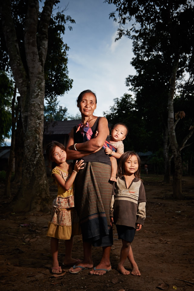 Grandmother with her three grandchildren posing for a quick picture. Notice by her facial expression how peaceful and happy she is