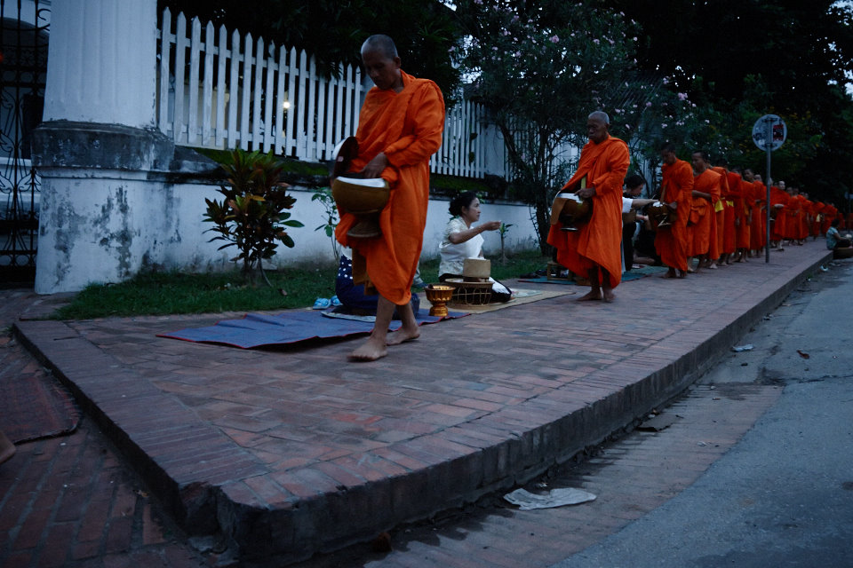 Before the sunrise, monks at Luang Prabang are being offerd alms for the day