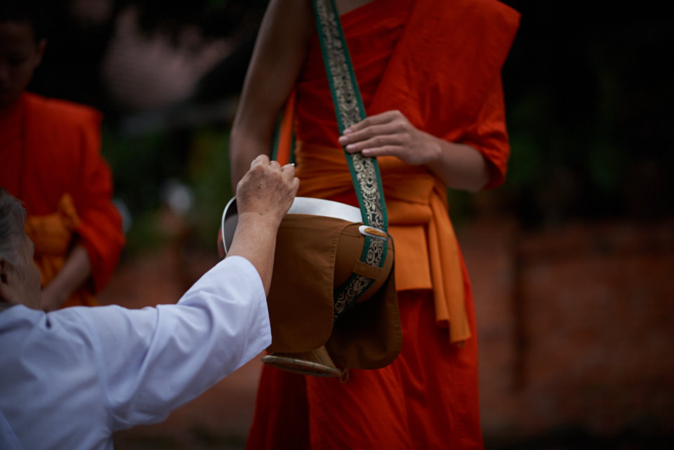 The alms are being placed in specially crafted pots being held by the monks